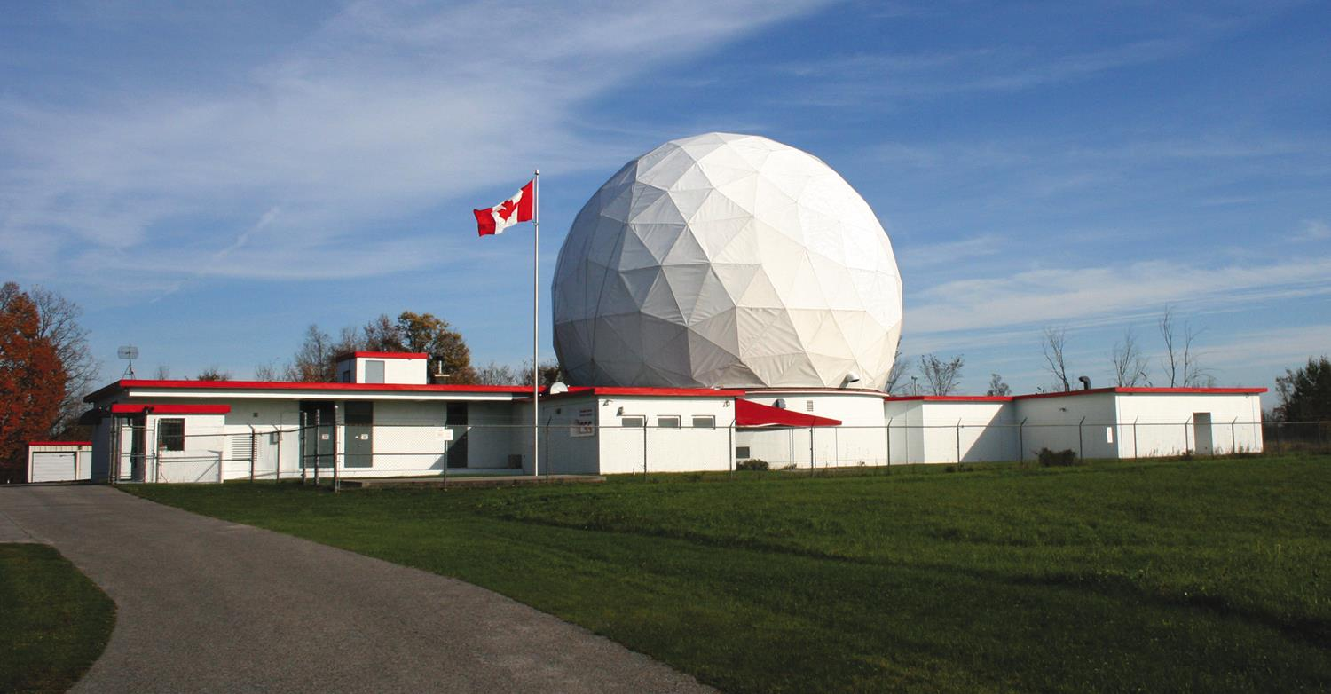 Exterior view of a building with a giant metal space frame radar dome on its roof.