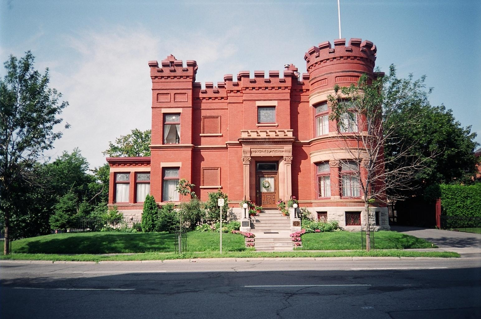 Exterior photo of a red brick two-storey mansion that resembles a castle with a corner turret.