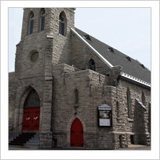 Exterior view of a stone Gothic Revival church with two red doors built in 1887.