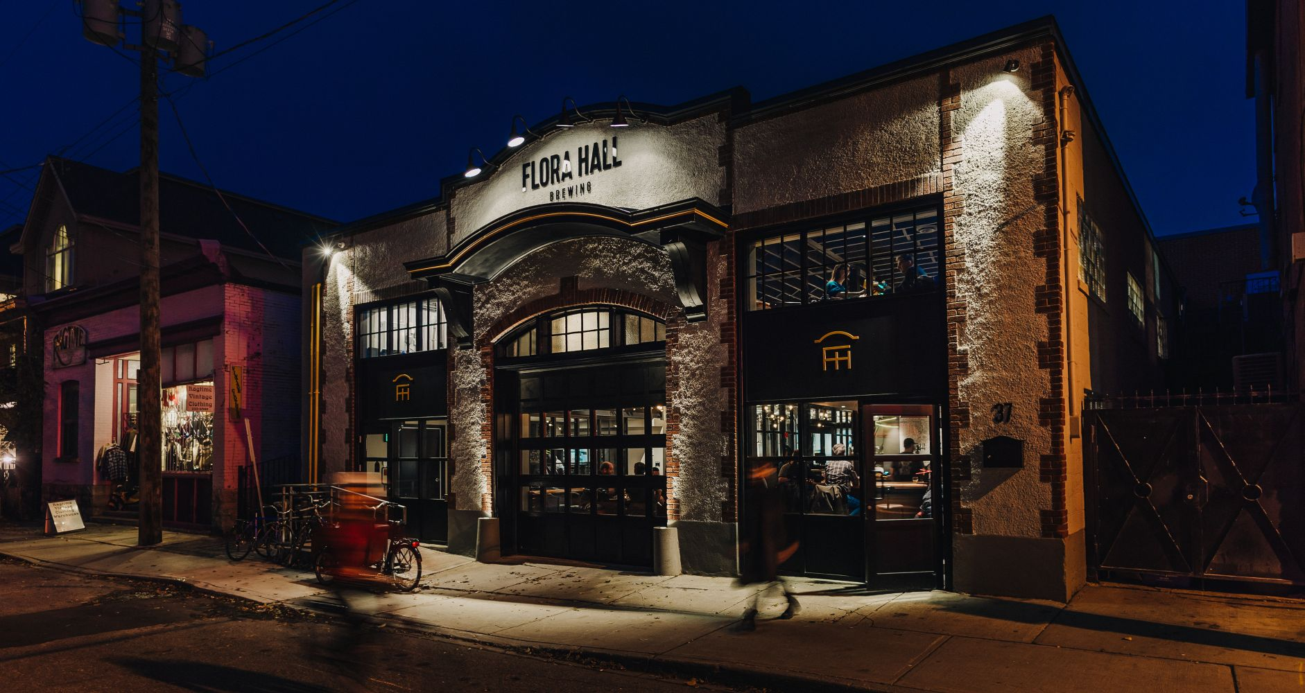Exterior evening view of the Flora Hall Brewing building, a former 1960s garage.