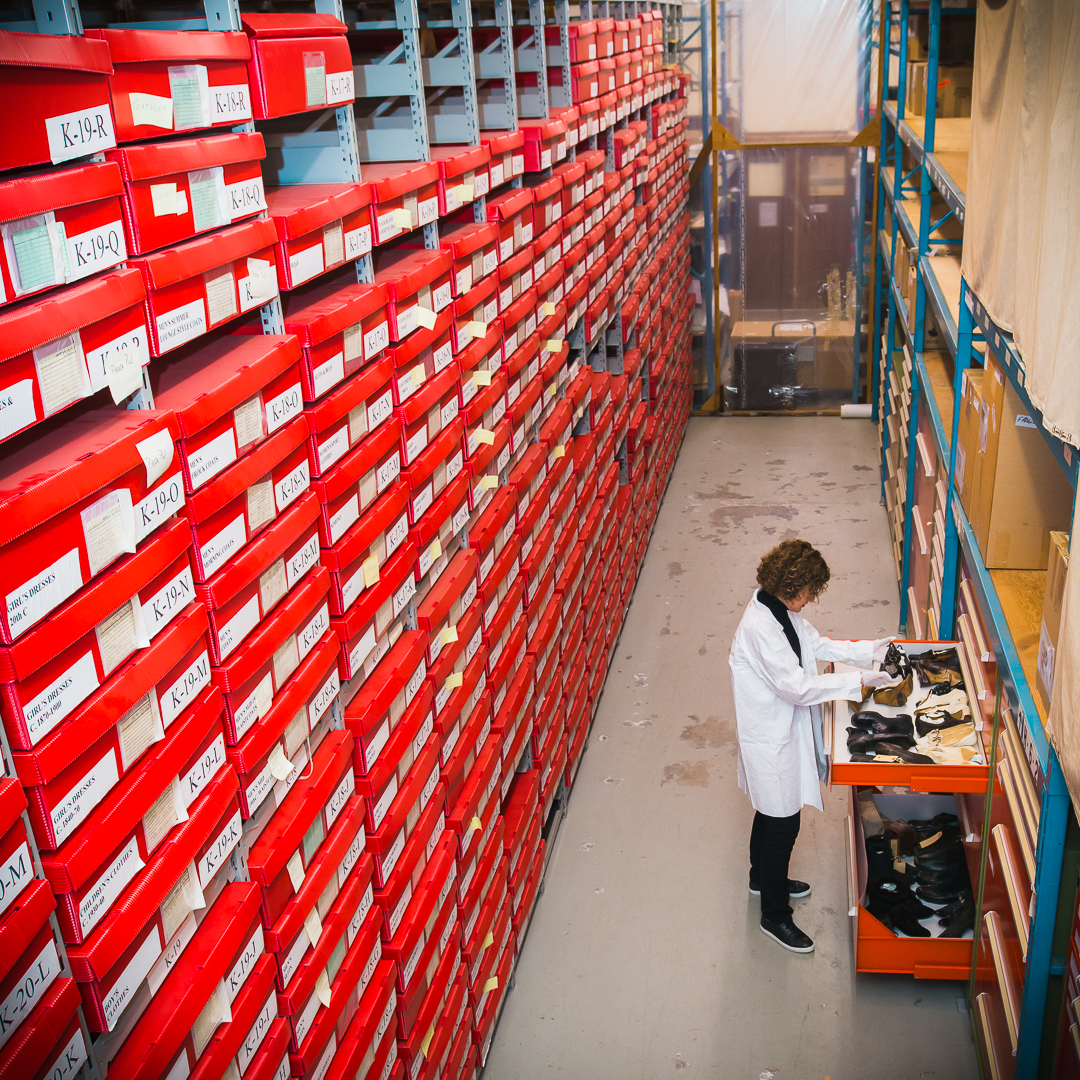 Interior photo of the Parks Canada artefact collection storage, and a collections officer handling artefacts.
