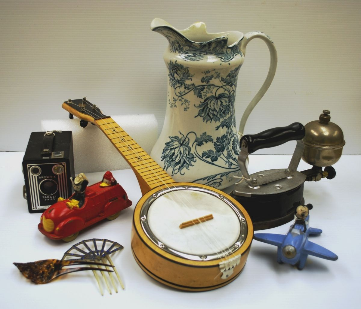 Picture of several artefacts from the Gloucester collection, including a banjo, a pitcher, and a toy airplane.