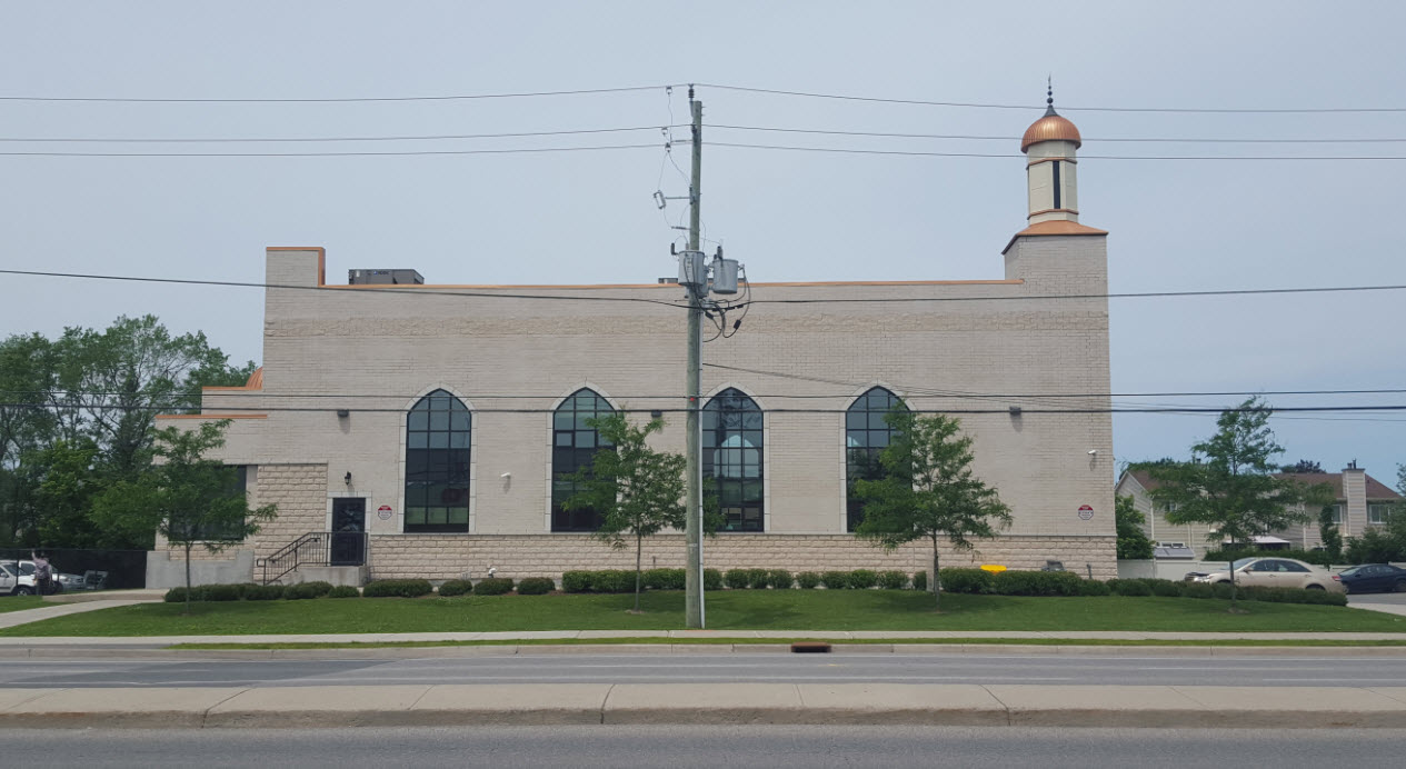 Exterior view of a modern mosque featuring expansive arched windows, reminiscent of those found in Spain.