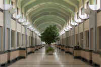 Interior photo of the art deco water treatment plant that showcases high arched ceilings and potted trees along the centre of the corridor.