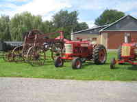 Exterior photo of the red brick museum in the background and old farming equipment in the foreground.