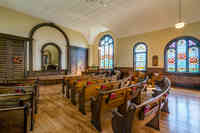 Interior photo of rows of wooden pews, several stained glass windows, and beautifully maintained hardwood floors.