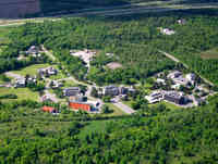 Aerial view of the CanmetENERGY complex featuring multiple buildings surrounded by a forested area.