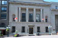 Exterior view of a former bank that incorporates Canadian motifs in the carved frieze.