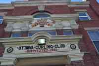 Exterior view of the front entrance of the curling club, featuring red brick with beige trim and the words Ottawa Curling Club above the door.