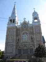 Exterior view of a century-old stone church built in Gothic style with Romanesque features.